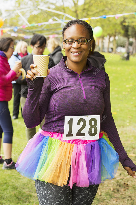 Portrait smiling runner in tutu drinking water