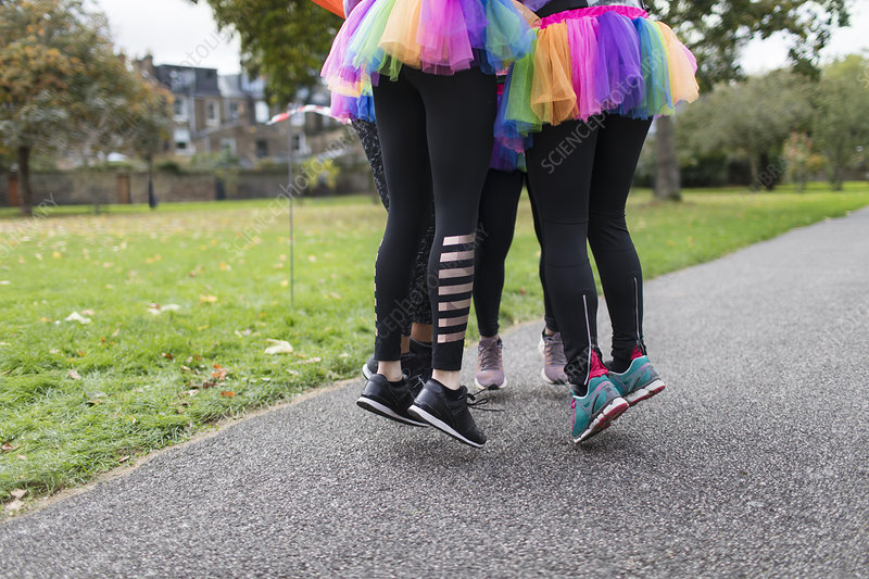 Enthusiastic runners in tutus jumping on park path