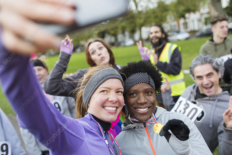Smiling female runners with medal taking selfie