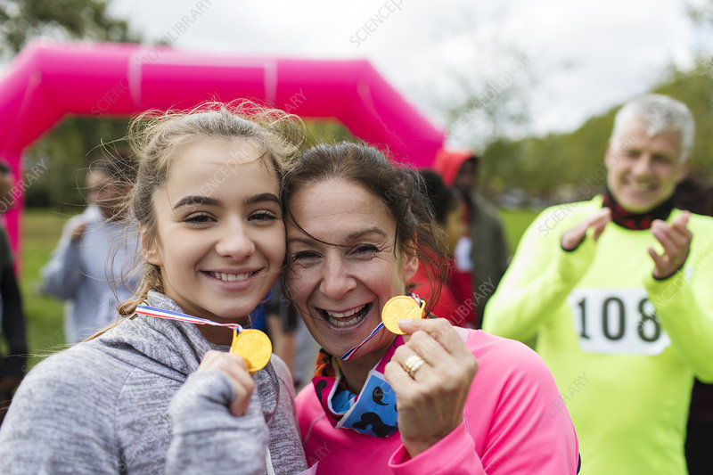 Mother and daughter runners showing medals