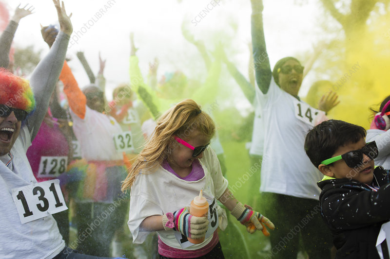 Playful crowd of runners throwing Holi powder