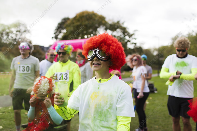 Playful boy runner in wig covered in Holi powder