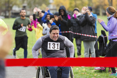 Man in wheelchair nearing race finish line