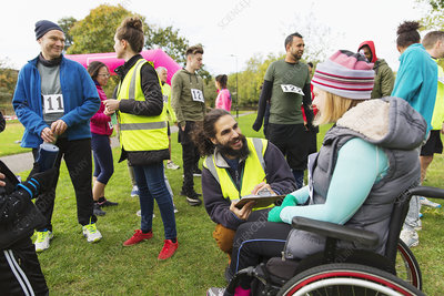 Woman in wheelchair checking in with volunteer