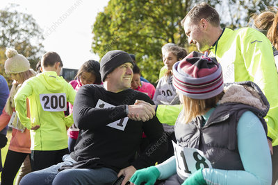 Runner shaking hands with man in wheelchair