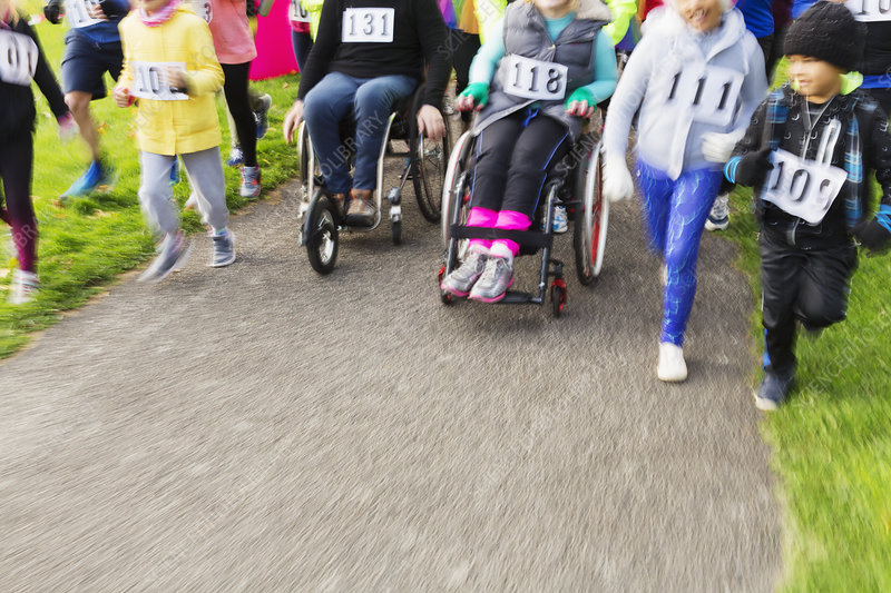 People in wheelchairs and runners moving