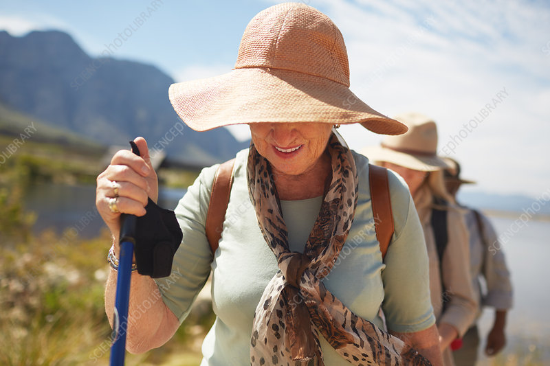 Active senior woman in sun hat hiking
