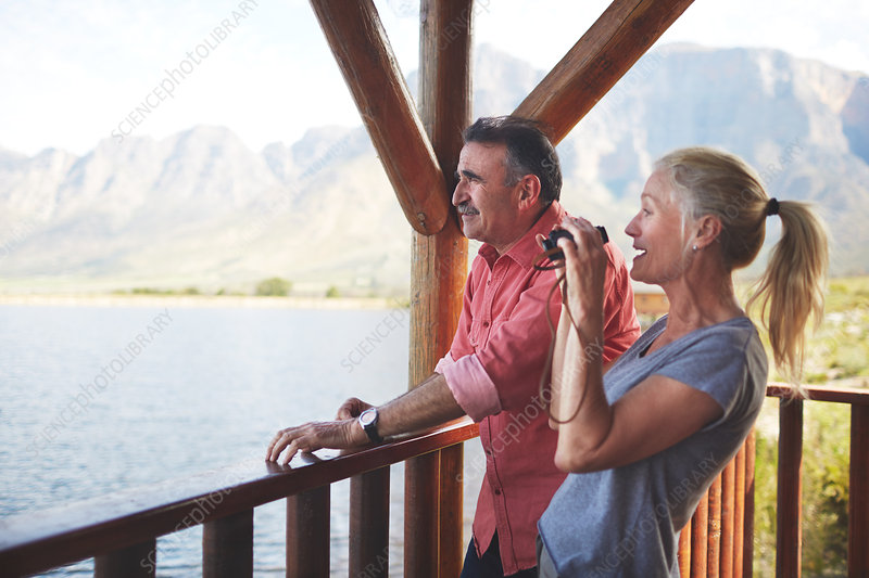 Couple with binoculars enjoying lake view