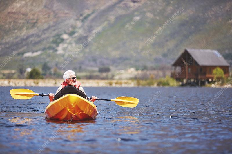 Senior man kayaking on sunny summer lake