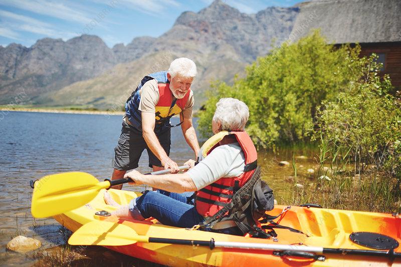 Active senior couple kayaking on sunny summer lake