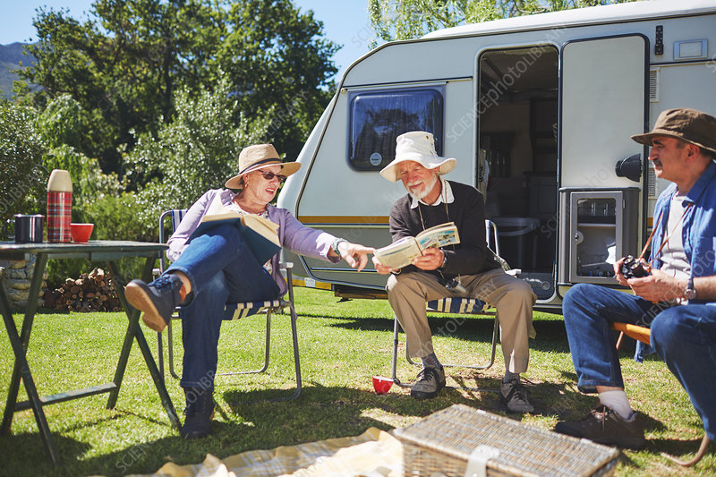 Active senior friends reading outside camper van