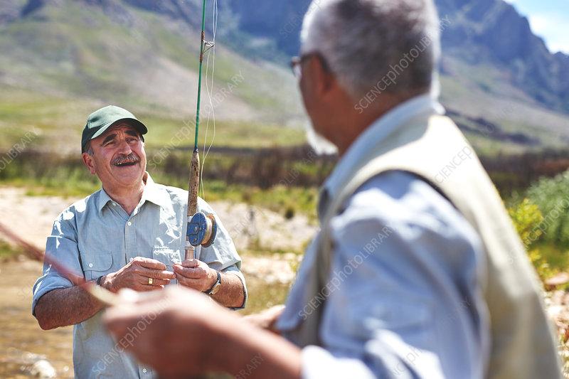 Smiling active senior men fishing