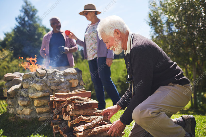 Active senior man stacking firewood