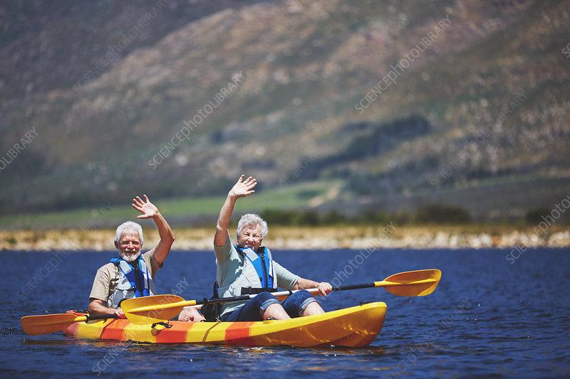 Portrait active senior couple in kayak waving