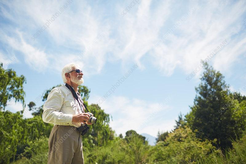 Curious active senior man looking up