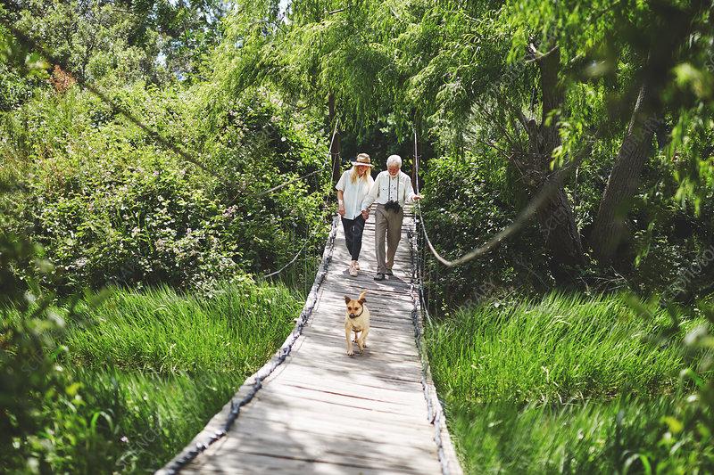 Active senior couple and dog crossing footbridge