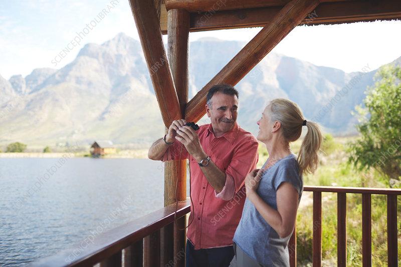 Happy couple with binoculars enjoying lake view