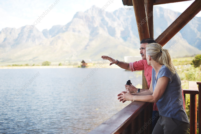 Couple with binoculars looking at lake view
