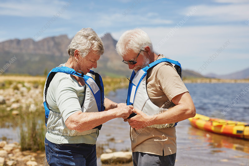 Active senior couple putting on life jackets