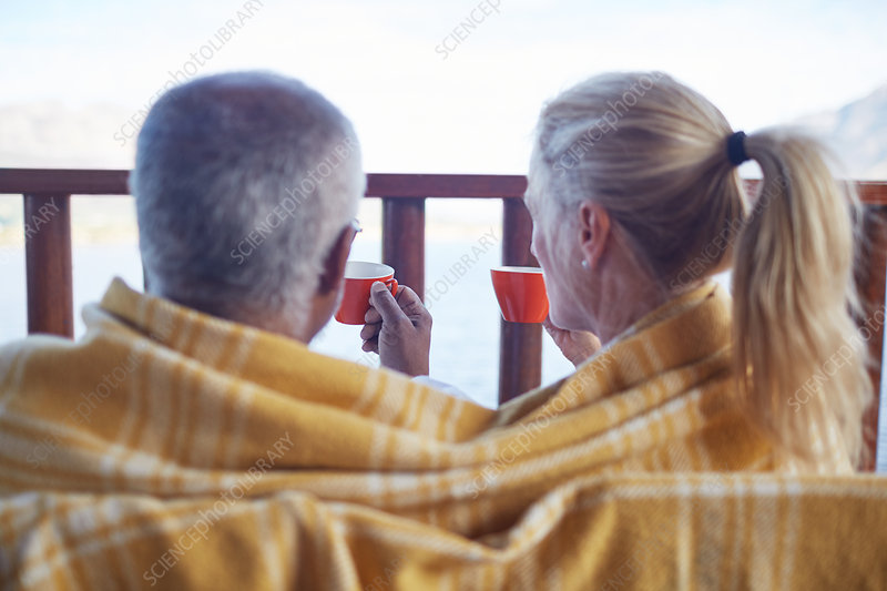 Cosy couple wrapped in blanket, drinking coffee