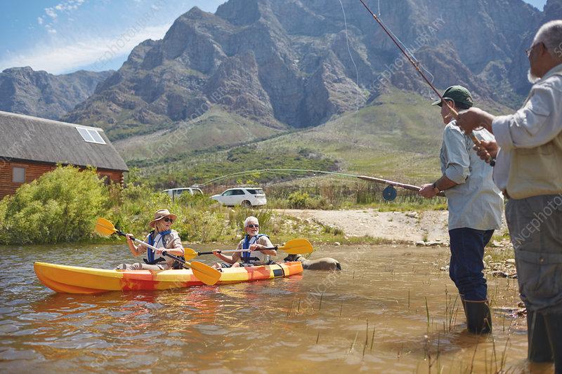 Active senior friends fishing and kayaking
