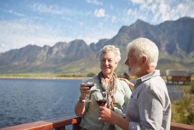 Smiling active senior couple drinking red wine