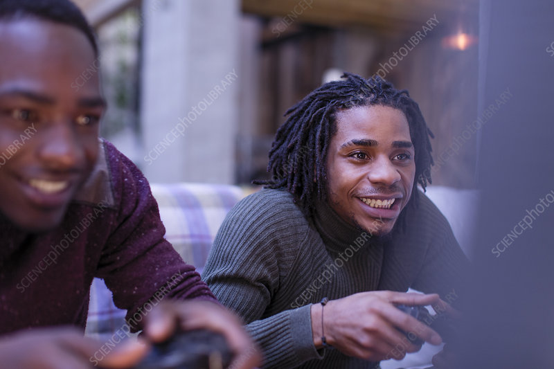Enthusiastic young men friends playing video game