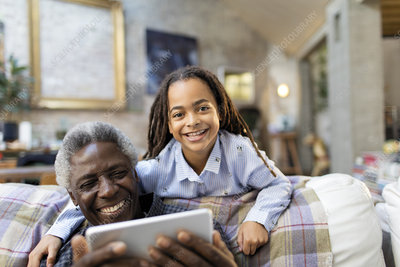 Portrait grandfather and granddaughter with tablet