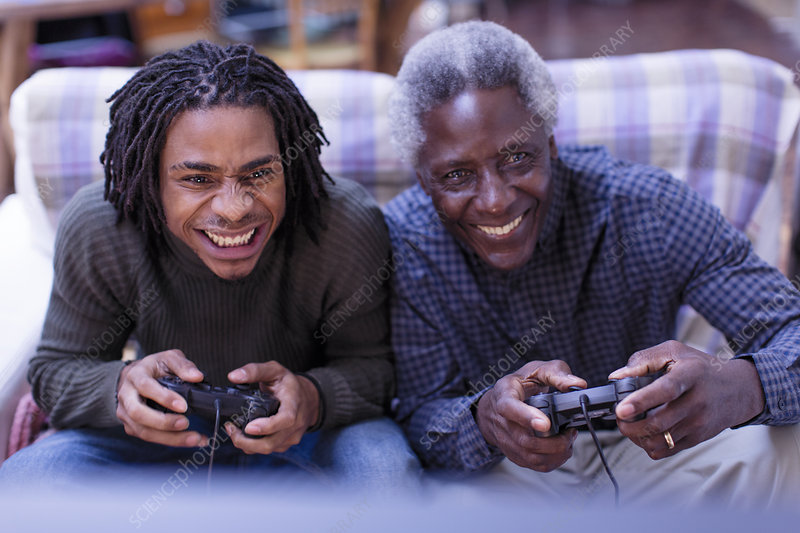 Happy grandfather and grandson playing video game