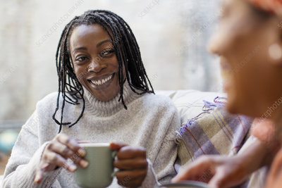 Woman listening to friend and drinking coffee