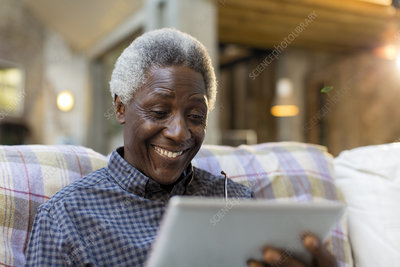 Smiling senior man using digital tablet on sofa