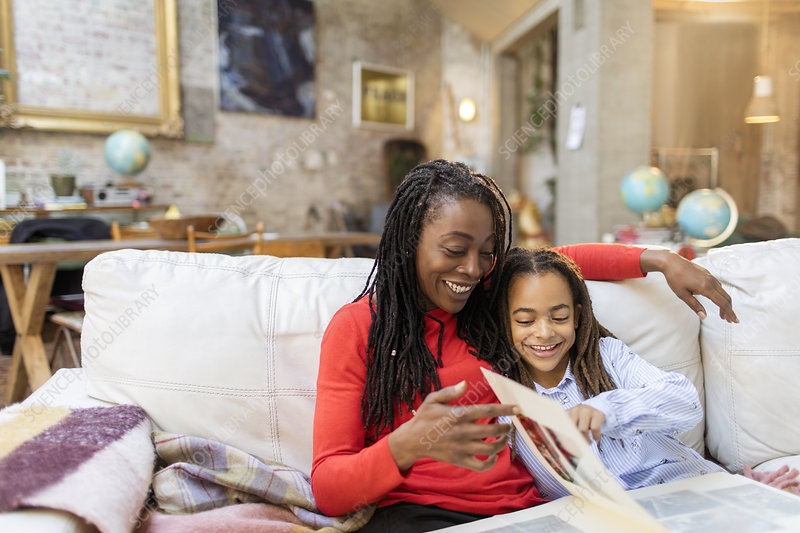 Mother and daughter looking at photo album on sofa
