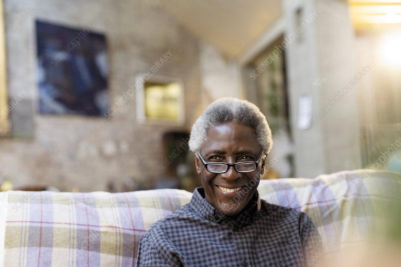 Portrait smiling, confident senior man on sofa