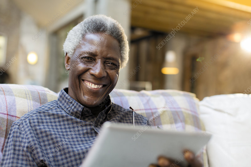 Portrait smiling, senior man using tablet on sofa