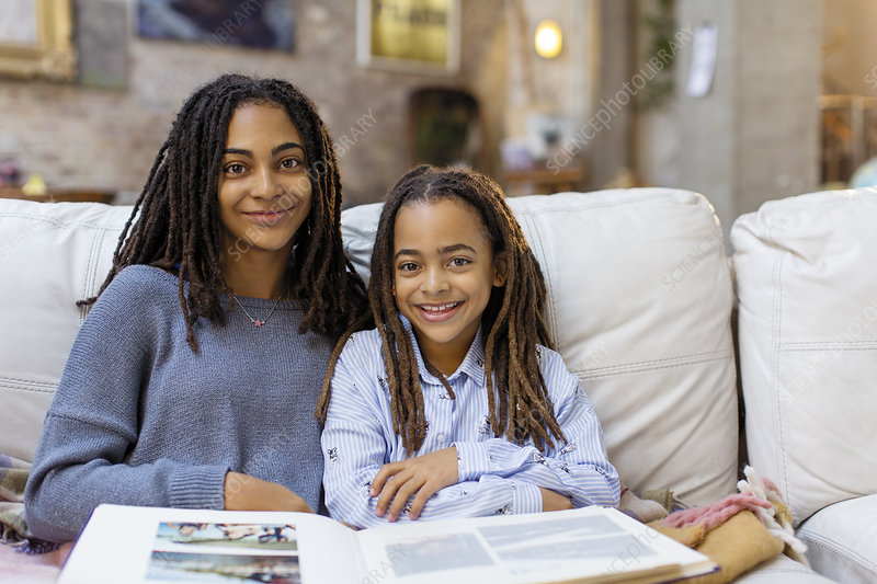 Portrait smiling, sisters with photo album on sofa