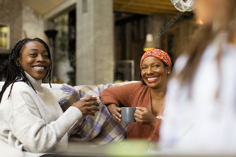 Smiling women talking and drinking coffee on sofa