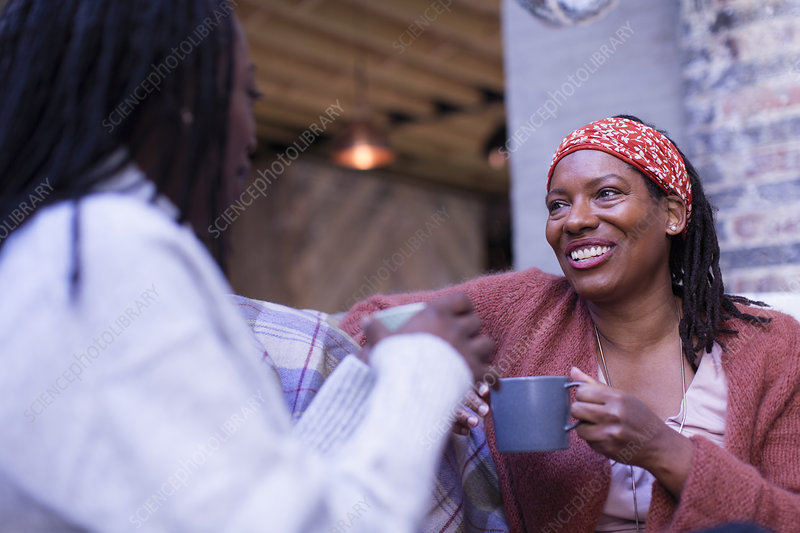 Smiling women friends talking and drinking coffee