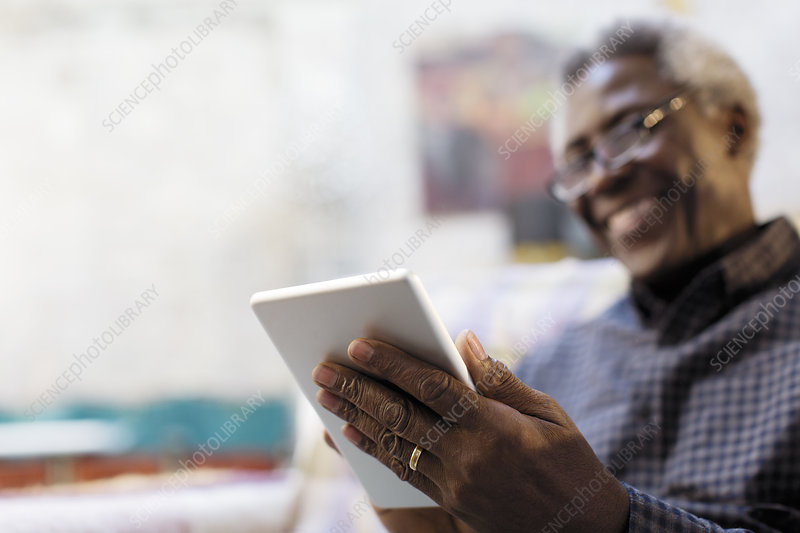 Smiling senior man using digital tablet