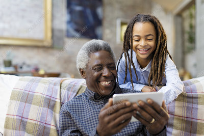 Grandfather and granddaughter using smart phone