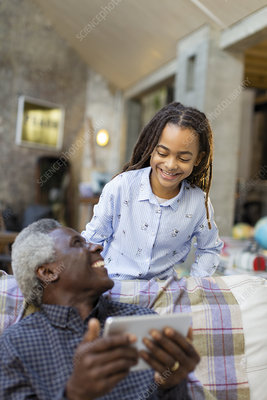 Smiling grandfather and granddaughter using tablet
