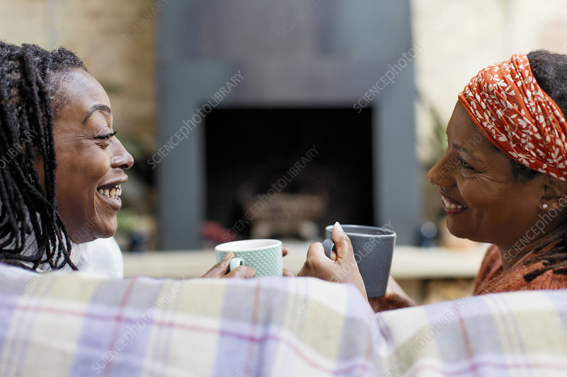 Smiling women friends talking and drinking tea