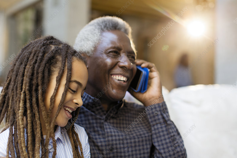 Grandfather and granddaughter talking on cellphone