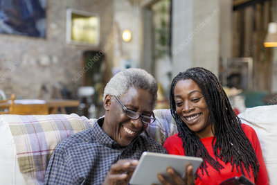 Daughter showing senior father how to use tablet