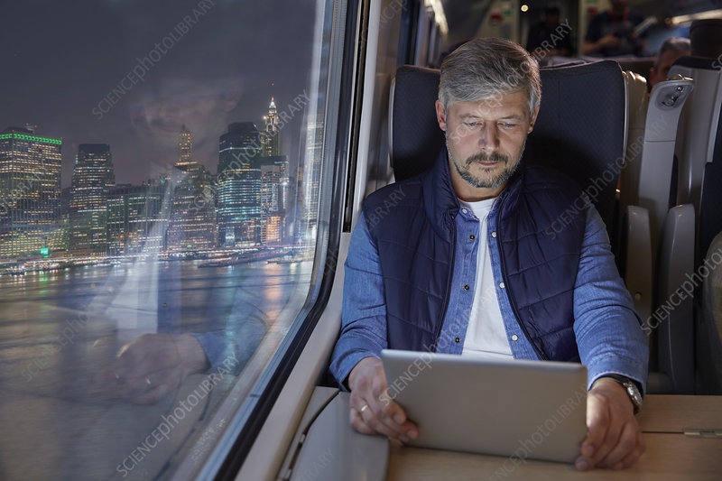 Man using digital tablet on train at night