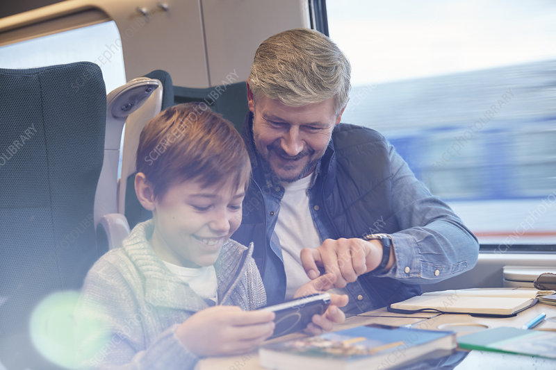 Father and son using smart phone on train