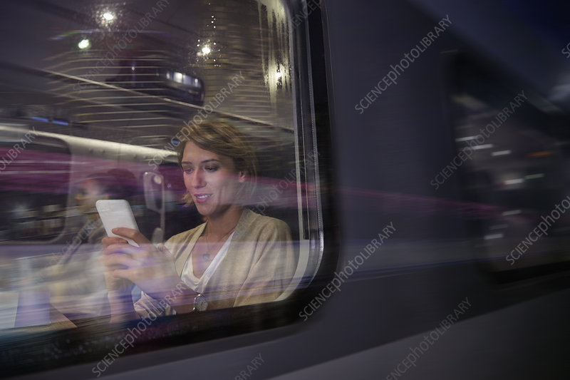 Businesswoman using smart phone on train at night