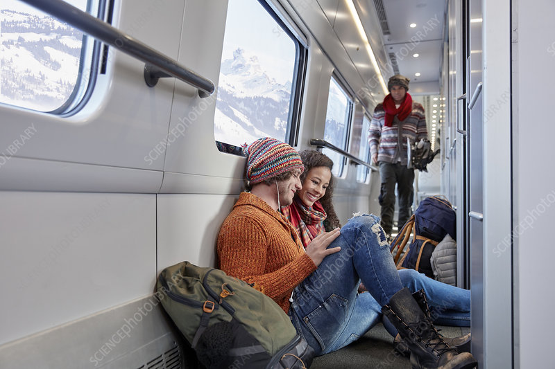 Young couple backpacking, riding train