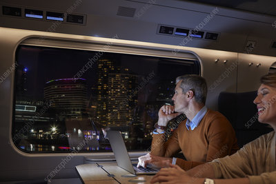 Businessman working at laptop on train