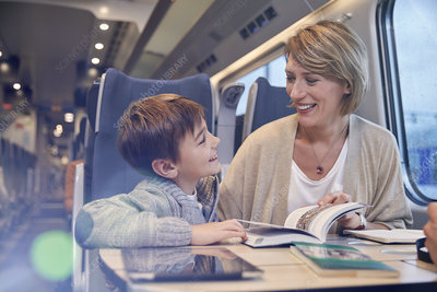 Mother and son reading travel guidebook on train