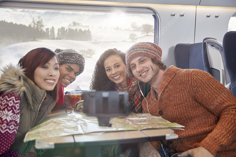Young friends with map taking selfie on train